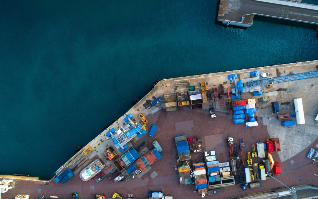 Photo of trucks and containers by body of water, all part of a supply chain.